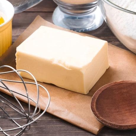 Satu blok mentega dikelilingi perkakas baking dan telur serta terigu