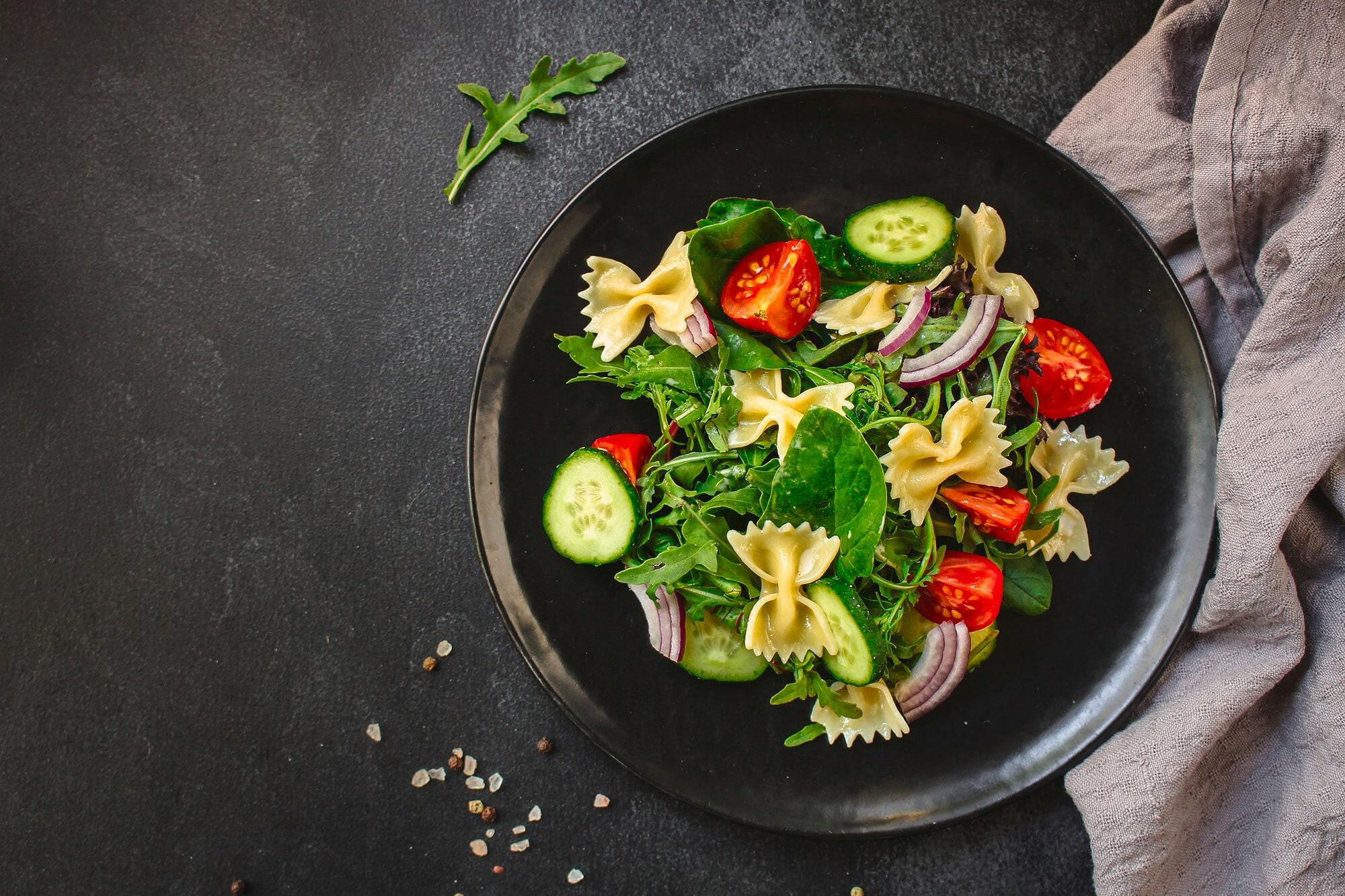 Salad zucchini, tomat, rocket, dan farfalle disajikan dalam mangkuk hitam