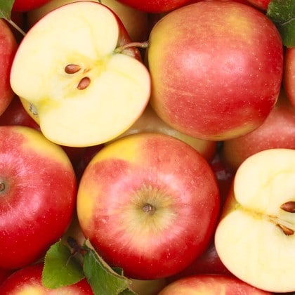 Buah apel merah bertumpuk dengan cantik, salah satunya terbelah dua
