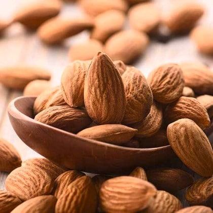 Butiran kacang almond di dalam sendok kayu dan papan kayu