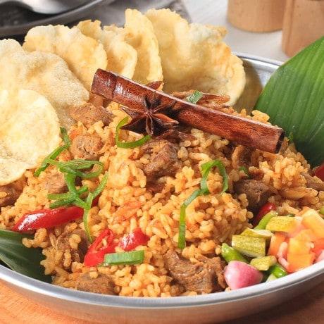 Nasi kebuli disajikan dalam piring logam dan ditemani dengan emping