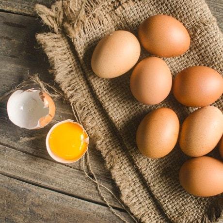 Telur ayam kampung dan telur ayam negeri di dalam mangkuk dan di atas serbet kotak-kotak