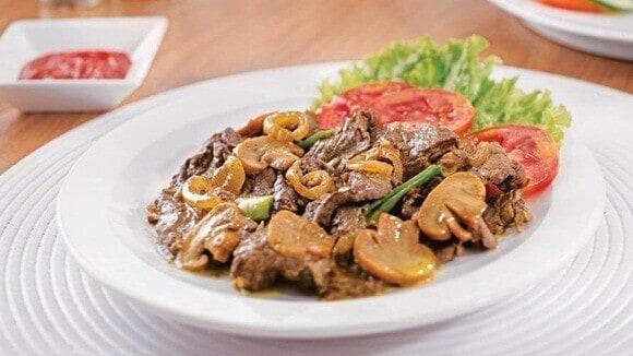 Tumis sapi jamur disajikan di atas meja makan